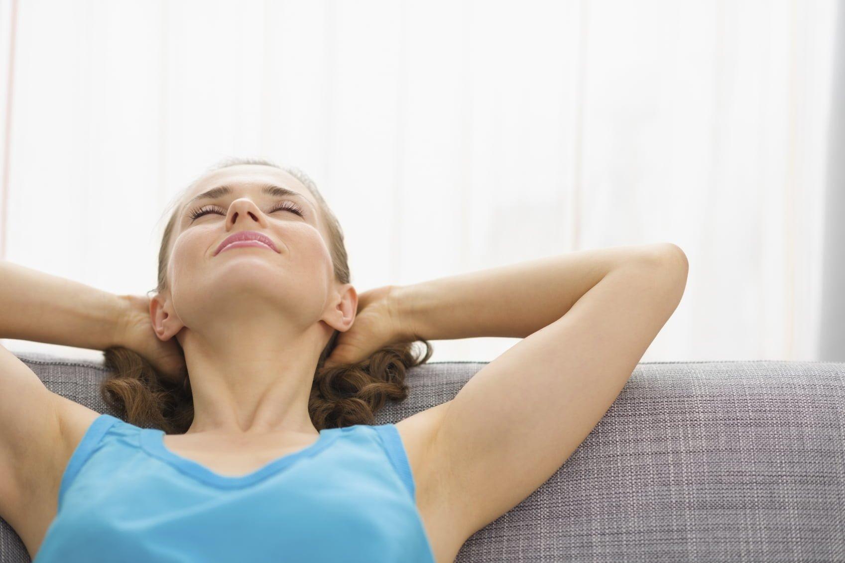Jeune femme qui relaxe sur son canapé