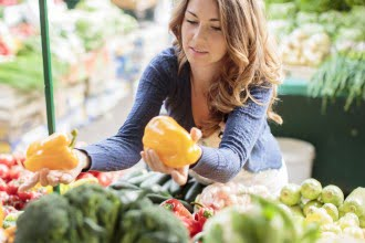 Young woman choosing between two yellow peppers at the supermarket