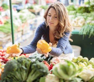 Jeune femme hésitant entre deux poivrons jaune au supermarché