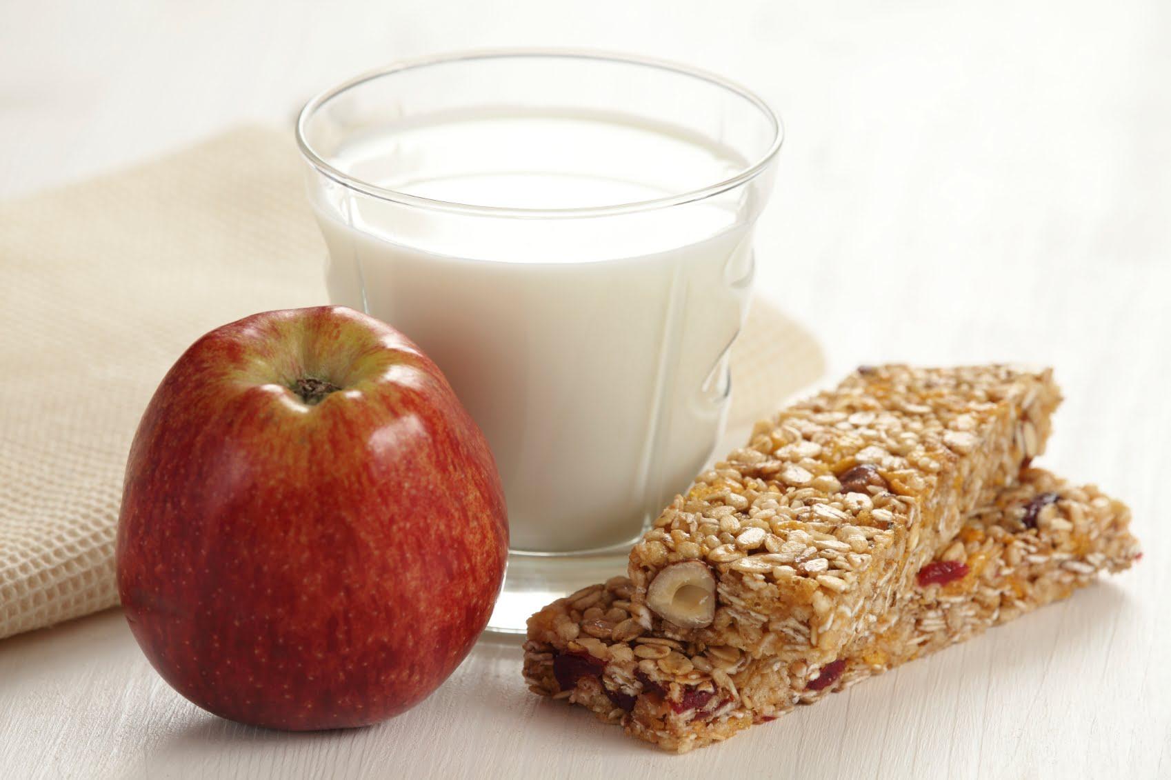 Barre granola avec verre de lait et pomme