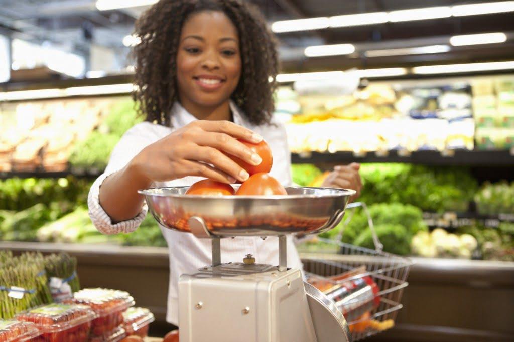 Woman weighing food at supermarket